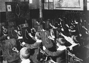 IMAGEM: Foto em preto e branco de uma turma de crianças numa aula de desenho que copiam exatamente a mesma imagem do quadro em suas telas.