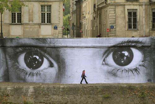 IMAGEM: A foto mostra um muro que tem como imagem dois olhos e à frente dele uma pessoa andando
