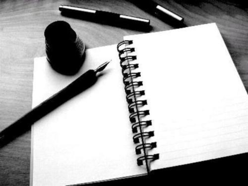 IMAGEM: A foto em, preto e branco, mostra um caderno espiral aberto. Sobre o caderno,  uma caneta e tinta (carga). Não há nada escrito nas páginas.