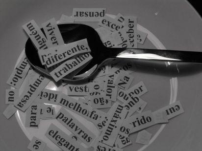 DESCRIÇÃO DE IMAGEM: dentro de um prato, há palavras recortadas em pequenos papeis. Também há uma colher que destaca palavras como diferente, trabalho e viver.