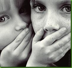 Descrição da Imagem: close no rosto de duas crianças que têm suas mãos fechando suas bocas.