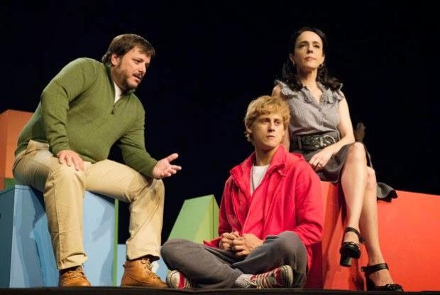 DESCRIÇÃO DA IMAGEM:  A foto é um retrato de uma das cenas da peça. Os pais do adolescente estão sentados e o jovem está sentado no chão.