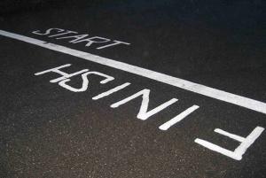 DESCRIÇÃO DA IMAGEM: foto do asfalta com uma linha branca marcando de um lado a largada e do outro a chegada.