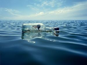DESCRIÇÃO DA IMAGEM: Foto mostra uma garrafa de vidro transparente com uma pessoa dentro à deriva em um mar calmo com céu azul.