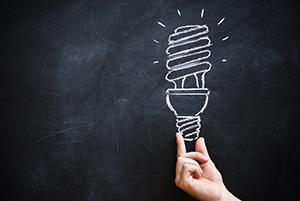 DESCRIÇÃO DA IMAGEM: Um quadro, negro, com uma lâmpada desenhada a giz. Abaixo do desenho, uma mão que simula segurar a lampada