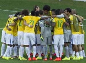 DESCRIÇÃO DA IMAGEM: Foto mostra o time do Brasil reunido em círculo no gramado.