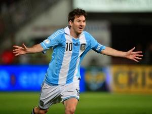 DESCRIÇÃO DA IMAGEM: Foto do jogador de futebol Messi da Argentina no gramado do campo correndo de braços abertos em comemoração ao gol que fez.