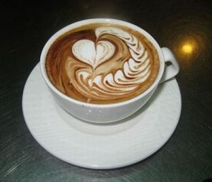 DESCRIÇÃO DA IMAGEM: Foto de uma xícara de café com espuma de leite, onde se misturam o marrom do café com o branco do leite formando um coração.