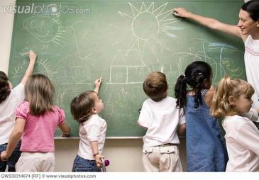 DESCRIÇÃO DA IMAGEM:  professora desenha no quadro junto com seis crianças