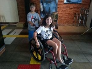 DESCRIÇÃO DA IMAGEM: a foto mostra um menino com síndrome de down empurrando uma menina na cadeira de rodas.