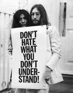 """DESCRIÇÃO DA IMAGEM: foto em preto e branco de John Lennon e Yoko Ono segurando um cartaz que diz em inglês""""Não odeie o que você não compreende"""""""