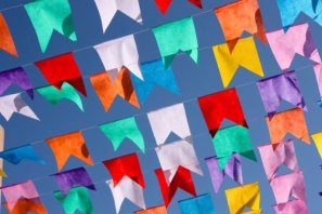 DESCRIÇÃO DA IMAGEM: A foto mostra várias bandeirinhas, de diferentes cores, de festa junina.