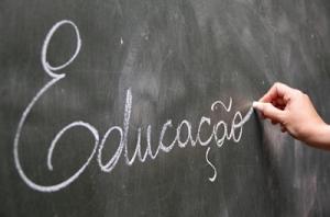 Descrição da imagem: Foto que mostra um quadro negro onde uma mão aparece escrevendo a palavra Educação com giz.